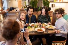 Amis avec le smartphone fotographing au restaurant Photographie stock libre de droits