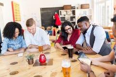 Amis avec le smartphone, le PC de comprimé et la bière à la barre Photographie stock