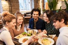 Amis avec le smartphone mangeant au restaurant Images libres de droits