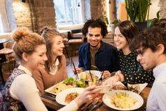 Amis avec le smartphone mangeant au restaurant Photo libre de droits