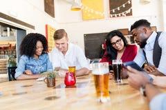 Amis avec le smartphone, le PC de comprimé et la bière à la barre Image libre de droits