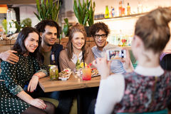 Amis avec le smartphone photographiant au café Photographie stock libre de droits
