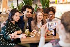 Amis avec le smartphone photographiant au café Photo libre de droits