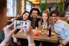 Amis avec le smartphone photographiant au café Photos stock