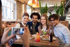 Amis avec le smartphone photographiant au café Photo stock