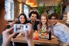 Amis avec le smartphone photographiant au café Photographie stock