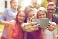 Amis avec le smartphone prenant le selfie à l'été Photo stock