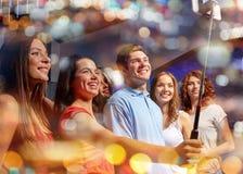 Amis avec le smartphone prenant le selfie dans la boîte de nuit Images stock