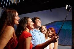 Amis avec le smartphone prenant le selfie dans le club Photos stock