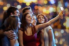 Amis avec le smartphone prenant le selfie dans le club Photographie stock libre de droits