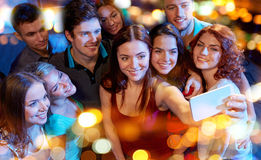 Amis avec le smartphone prenant le selfie dans le club Images libres de droits