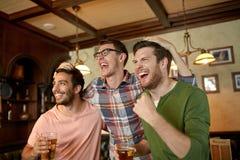Amis avec le sport de observation de bière à la barre ou au bar Photos libres de droits