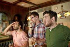 Amis avec le sport de observation de bière à la barre ou au bar Image libre de droits