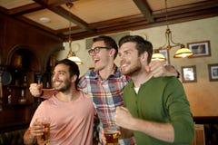Amis avec le sport de observation de bière à la barre ou au bar Image stock
