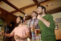 Amis avec le sport de observation de bière à la barre ou au bar Photos stock