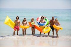 Amis avec les anneaux gonflables et radeaux de piscine sur le bord de la mer Image libre de droits