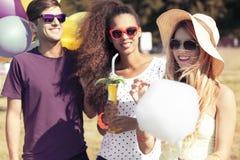 Amis avec les boissons et la sucrerie de coton Photo libre de droits
