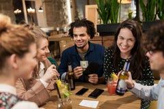 Amis avec les boissons, l'argent et la facture à la barre Image libre de droits