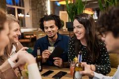 Amis avec les boissons, l'argent et la facture à la barre Images libres de droits