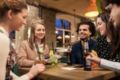 Amis avec les boissons, l'argent et la facture à la barre Photo libre de droits