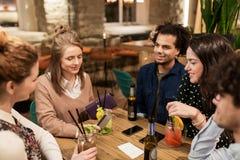 Amis avec les boissons, la carte de crédit et la facture à la barre Photo libre de droits