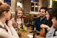 Amis avec les boissons, la carte de crédit et la facture à la barre Photographie stock