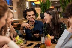 Amis avec les boissons, la carte de crédit et la facture à la barre Photos libres de droits