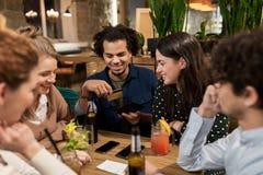 Amis avec les boissons, la carte de crédit et la facture à la barre Image stock
