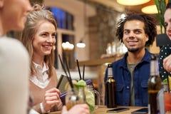 Amis avec les boissons, la carte de crédit et la facture à la barre Images libres de droits