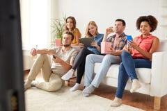 Amis avec les instruments et la bière regardant la TV à la maison Photographie stock