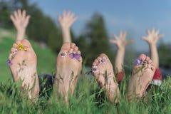 Amis avec les pieds nus se situant dans le domaine Images stock
