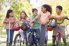 Amis avec les scooters et la planche à roulettes de bicyclettes Image libre de droits