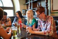 Amis avec les smartphones et la bière à la barre ou au bar Photographie stock