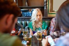 Amis avec les smartphones et la bière à la barre ou au bar Photos stock