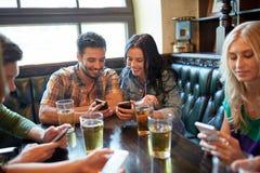 Amis avec les smartphones et la bière à la barre ou au bar Photo stock