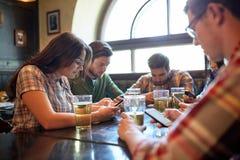 Amis avec les smartphones et la bière à la barre ou au bar Images libres de droits