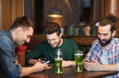 Amis avec les smartphones et la bière verte au bar Photo stock