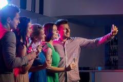 Amis avec les verres et le smartphone dans le club Photo stock