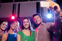 Amis avec les verres et le smartphone dans le club Photographie stock libre de droits