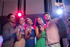 Amis avec les verres et le smartphone dans le club Image libre de droits
