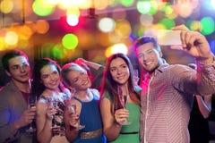 Amis avec les verres et le smartphone dans le club Photographie stock