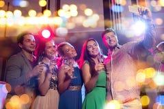 Amis avec les verres et le smartphone dans le club Images stock