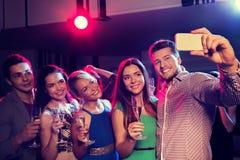 Amis avec les verres et le smartphone dans le club Photos stock