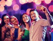Amis avec les verres et le smartphone dans le club Photo libre de droits