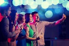 Amis avec les verres et le smartphone dans le club Image stock