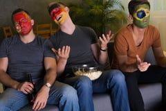 Amis avec les visages colorés observant le sport Images stock