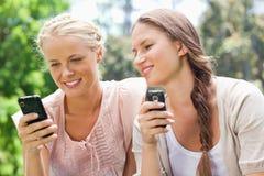 Amis avec leurs téléphones portables Image stock