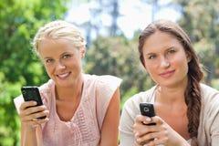 Amis avec leurs téléphones portables en parc Photos libres de droits