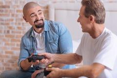Amis avec plaisir échangeant des consoles de jeu à la maison Images stock