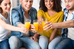 Amis avec plaisir buvant du jus Images stock